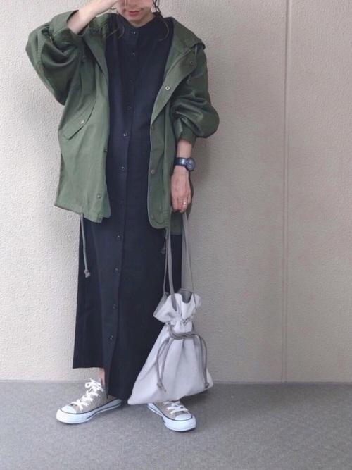 カーキモッズコートと黒バンドカラーガウンワンピースにグレースニーカーを履いた女性