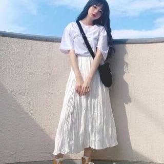 白ロゴショートスリーブTシャツと白ワッシャープリーツロングスカートにイエローハイカットスニーカーを履いた女性