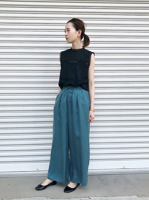 黒レースノースリーブにブルーワイドパンツを履いた女性