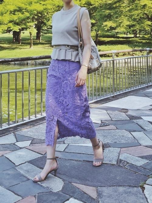 ベージュペプラムブラウスとワイドデザインベルトにパープルレーススカートを履いた女性