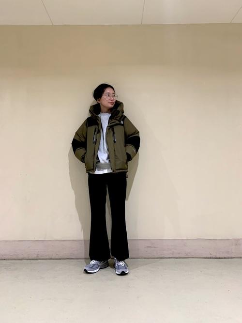 カーキダウンジャケットとブラックフレアパンツにニューバランスw990グレーを履いた女性