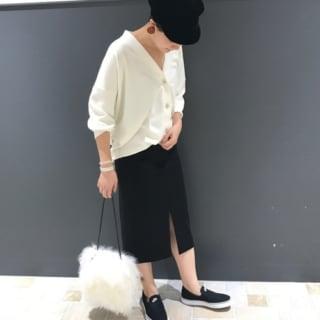 ホワイトVネックカーディガンとブラックスリットスカートにブラックナイキスリッポンを履いた女性
