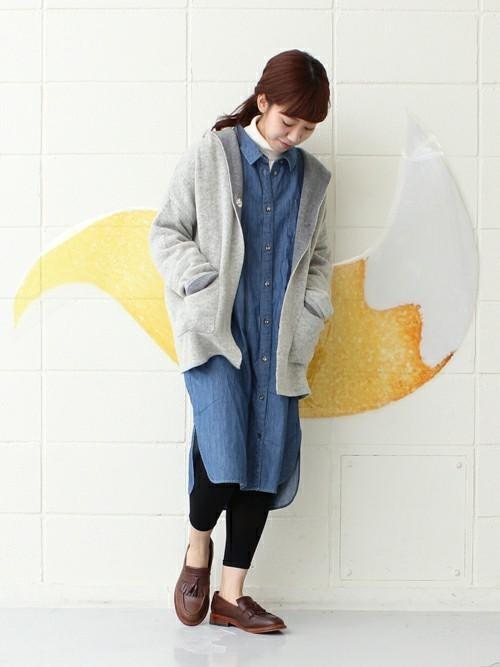 スリットデニムロングシャツとダブルフェイスフードコートにブラウンフリンジローファーを履いた女性