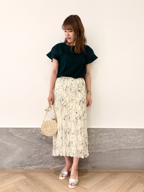 袖フリルトップスと花柄ワッシャープリーツスカートとスクエアトゥサンダルを履いた女性