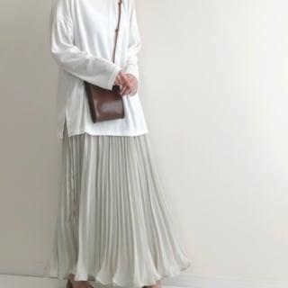 白ロングTシャツとロングプリーツスカートとブラウンフラットシューズのスカートコーデの女性