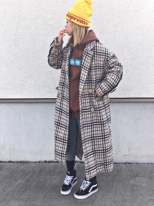 チェック柄コートとシュプリームのパーカーにグレーパンツを履いた女性