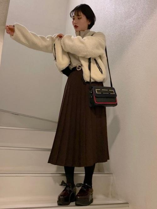 白ボアジャケットにプリーツスカートを履いた女性