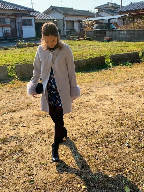 グレーノーカラーコートに花柄スカートを履いた女性