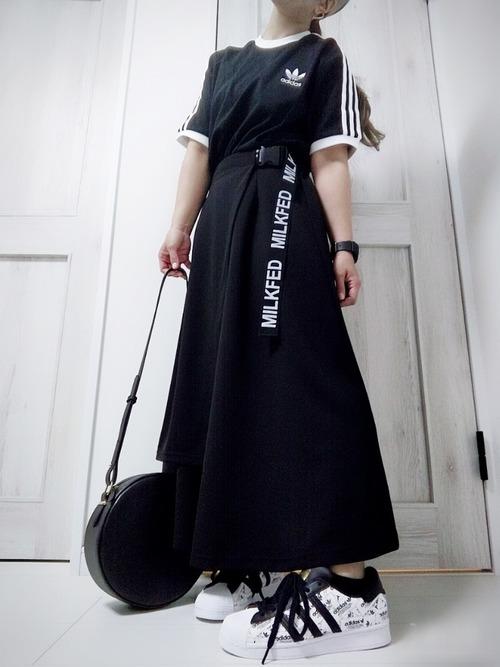 アディダスのスリーストライプTシャツとロゴスカートにアンパイアキャップを合わせた女性