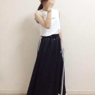 アディダスのロングサテンスカートとノースリーブTシャツにキャップを合わせた女性