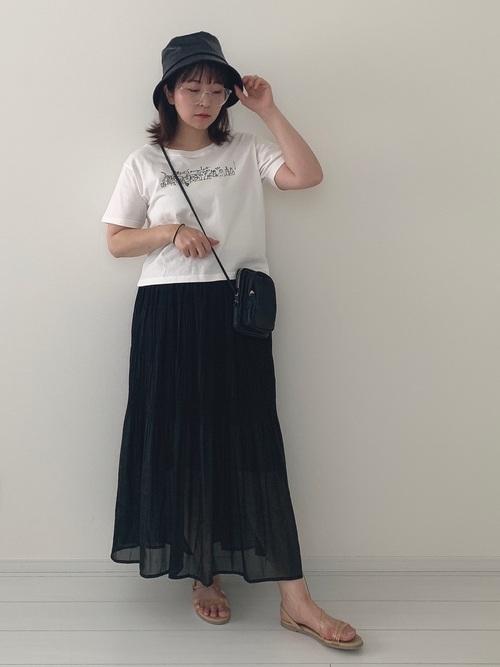 ホワイトTシャツとブラックプリーツロングスカートにベージュサンダルを履いた女性