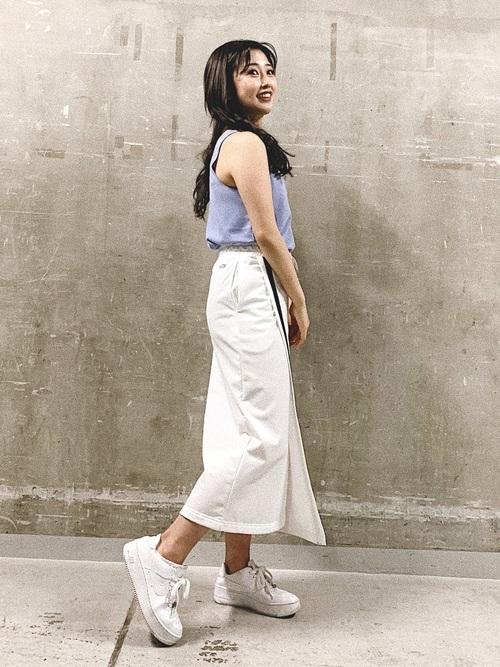 ヨガリュクスヘンリータンクトップとストレッチラインラップスカートに白スニーカーを履いた女性