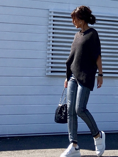 黒ケーブルニットとシルバーストレッチスキニーパンツにエクステンドソールスニーカーを履いた女性