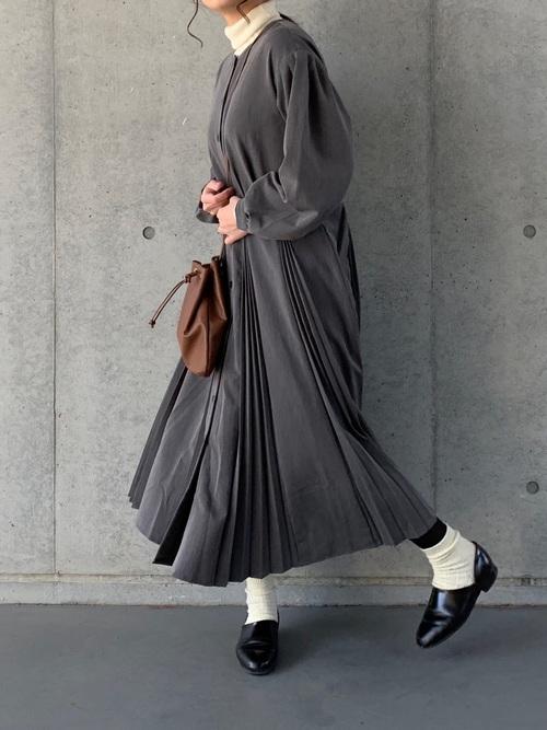 タックプリーツワンピースとハルタのローファースポックシューズにブラウン巾着バッグを持った女性