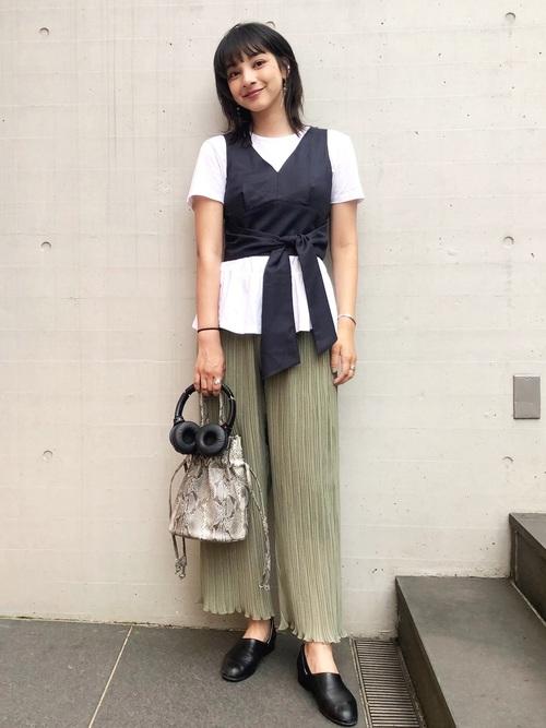 リボン付きビスチェとシフォンプリーツイージーパンツにハルタのローファースポックシューズを履いた女性