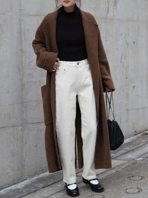 オーバーチェックコートとホワイトカラーデニムにハルタのローファーワンストラップシューズを履いた女性