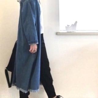 デニム裾フリンジコートとグレーパーカーに裾ゴムイージーパンツを履いた女性