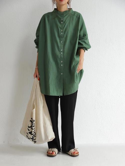 カーキスタンドカラービッグシャツと黒リブニットパンツにベージュサンダルを履いた女性