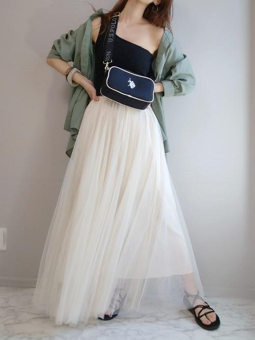 カーキバンドカラーフレアシャツと白チュールロングスカートに黒サンダルを履いた女性