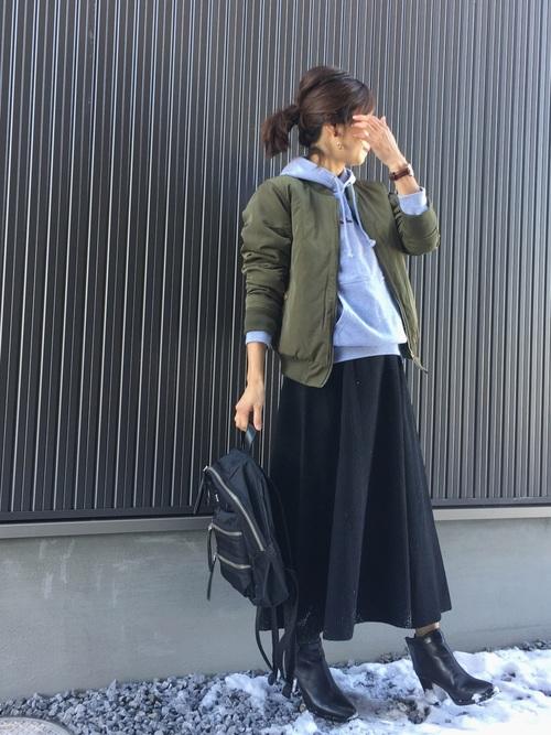 カーキMA-1と黒フレアスカートに黒ショートブーツを履いた女性