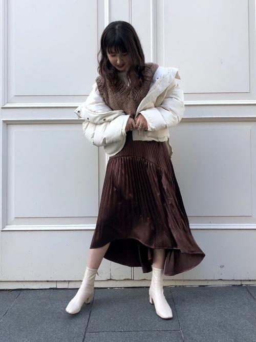 白ダウンジャケットとブラウンサテンプリーツフレアスカートに白ショートブーツを履いた女性