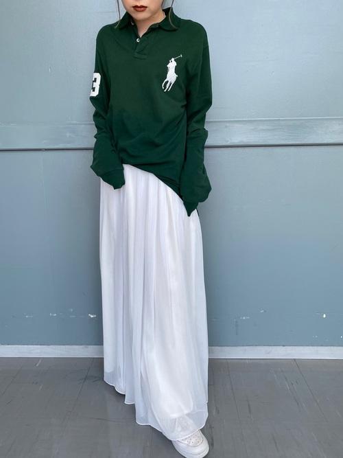 ラルフローレンのグリーン長袖ポロシャツと白ギャザーフレアスカートに白スニーカーを履いた女性
