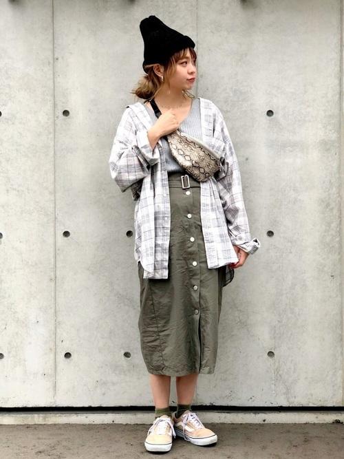 ラルフローレンのグレーチェックシャツとカーキフロントボタンタイトスカートにベージュスニーカーを履いた女性