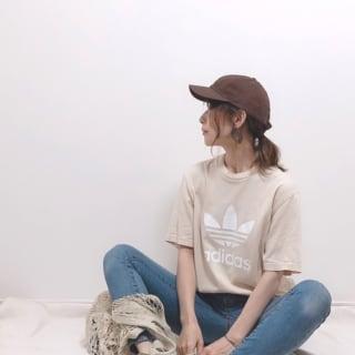 アディダスオリジナルスのベージュトレフォイルTシャツとスキニーデニムにウオッシュドキャンバススニーカーを履いた女性
