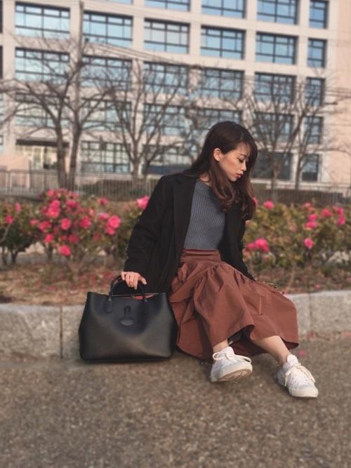 黒チュールチェスターコートとブラウンティアードロングスカートにロンシャンの黒ロゾ1986を持った女性