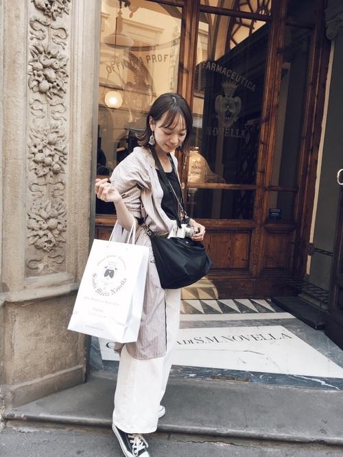 ベージュストライプ柄バンドカラーシャツワンピースと白ワイドパンツにロンシャンの黒 プリアージュネオショルダーバッグを持った女性