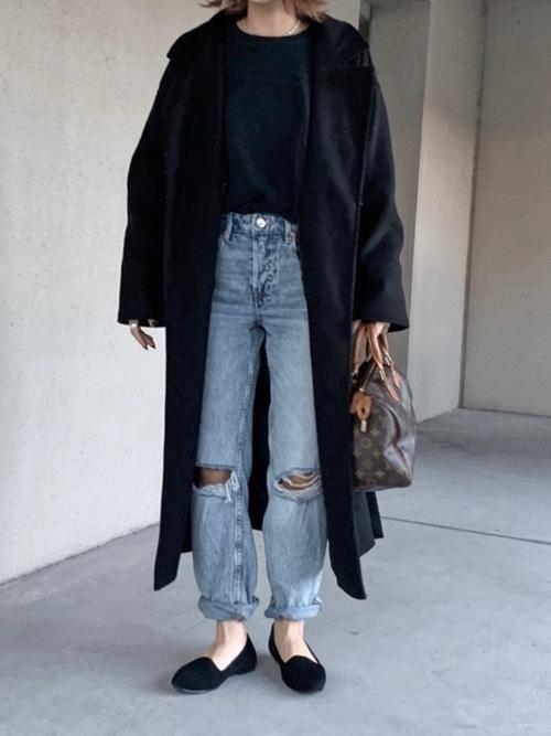 黒オーバーサイズロングチェスターコートとライトブルーストレートダメージデニムに黒オペラパンプスを履いた女性