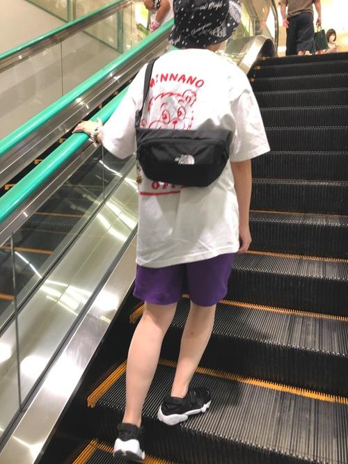 fcrbのハワイアンハットとホワイト半袖Tシャツとパープルハーフパンツの夏コーデの女性