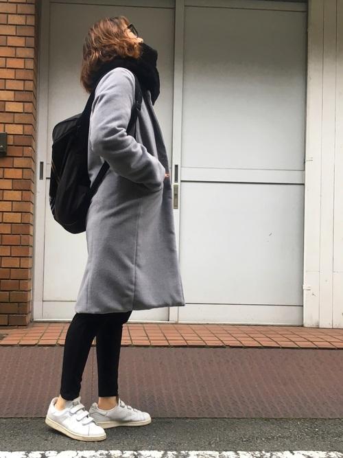 アディダスのスターウォーズコラボリュックとグレーのチェスターコートにブラックスキニーパンツを履いた女性