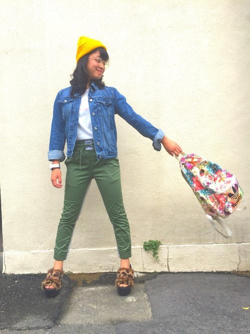 アディダスの花柄リュックとフェイド加工デニムジャケットにモスグリーンパンツを履いた女性