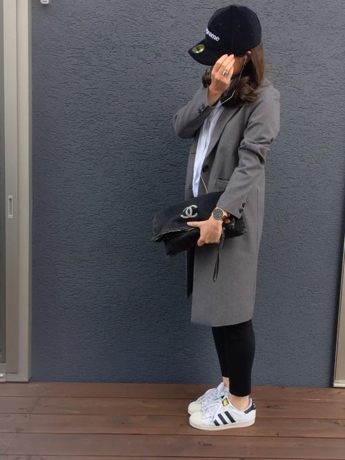 グレーチェスターコートと黒レギンスパンツに黒コーデュロイ刺繍ロゴキャップを履いた女性