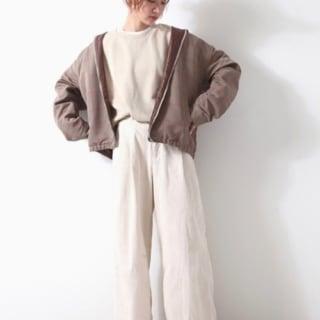 ベージュチェックスイングトップと白スウェットに白コーデュロイワイドパンツを履いた女性