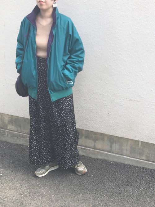 コロンビアのターコイズブルーマウンテンパーカーとベージュVネックニットに黒ドットロングスカートを履いた女性