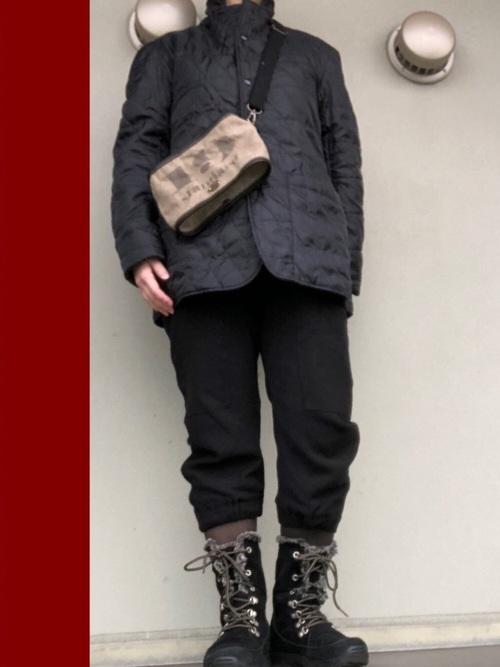 黒キルティングジャケットと黒ジョガーパンツにコロンビアの黒レースアップスノーブーツを履いた女性
