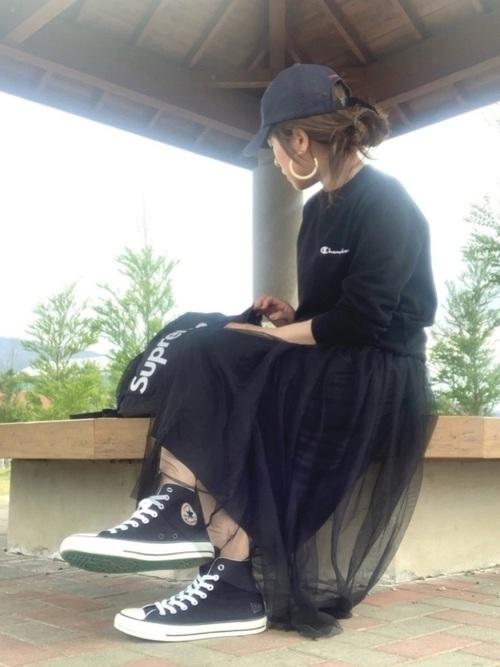 コロンビアのネイビーキャップと黒スウェットに黒チュールロングスカートを履いた女性