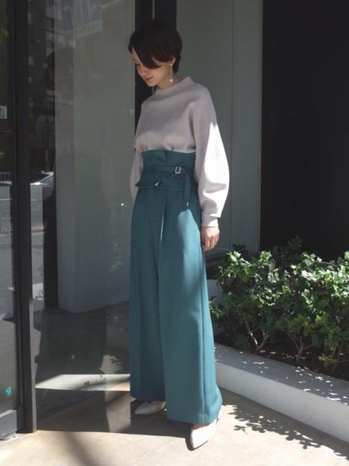 グレーボトルネックボリュームスリーブニットと緑コルセット付きワイドパンツにベージュパンプスを履いた女性