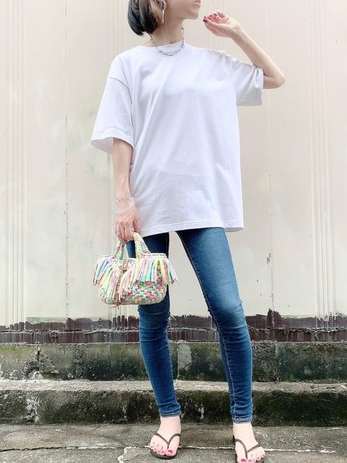 白ヘビーウェイトオーバーサイズTシャツとスキニージーンズにタイダイ柄フリンジバッグを合わせた女性