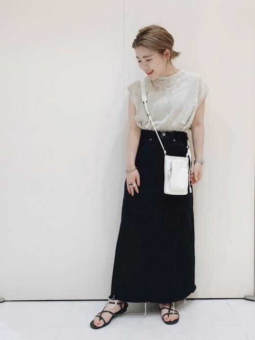 ベージュマーブルダイプルオーバーと黒ロングジーンズスカートに白ミニショルダーバッグを合わせた女性