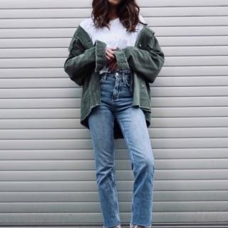 カーキコーデュロイジャケットとストレートデニムパンツにシルバーラメスニーカーを履いた女性