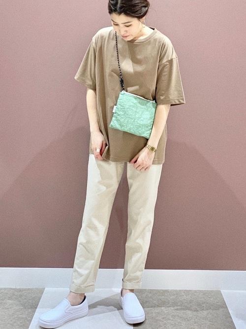 ブラウンオーバーサイズTシャツとアーバンリサーチの白リネン混イージーパンツに白スリッポンを履いた女性