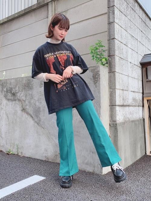 黒オーバーサイズバンドTシャツとグリーンセンタープレスフレアパンツに黒レザー厚底スニーカーを履いた女性