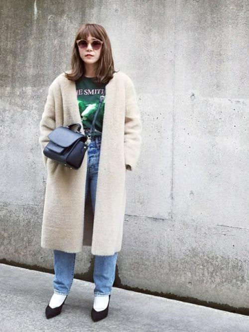 白ボアロングコートとグリーンバンドTシャツにブルースリムストレートデニムを履いた女性