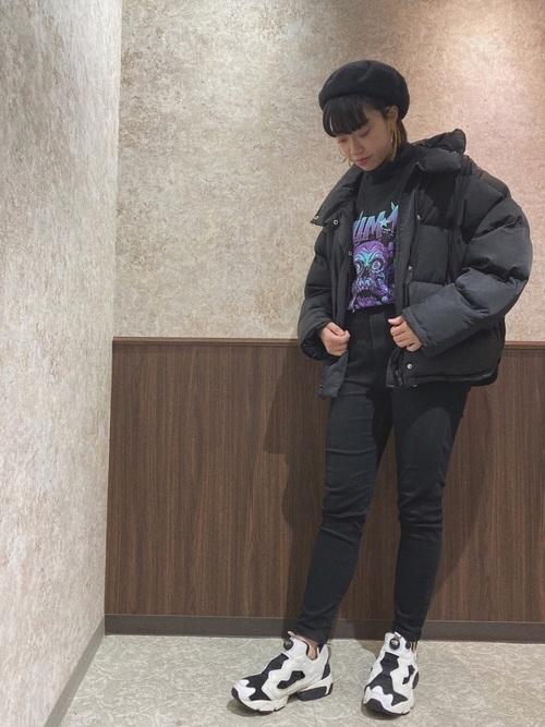 黒中綿ハイネックジップアップジャケットと黒バンドTシャツに黒クロップド丈スキニーデニムを履いた女性