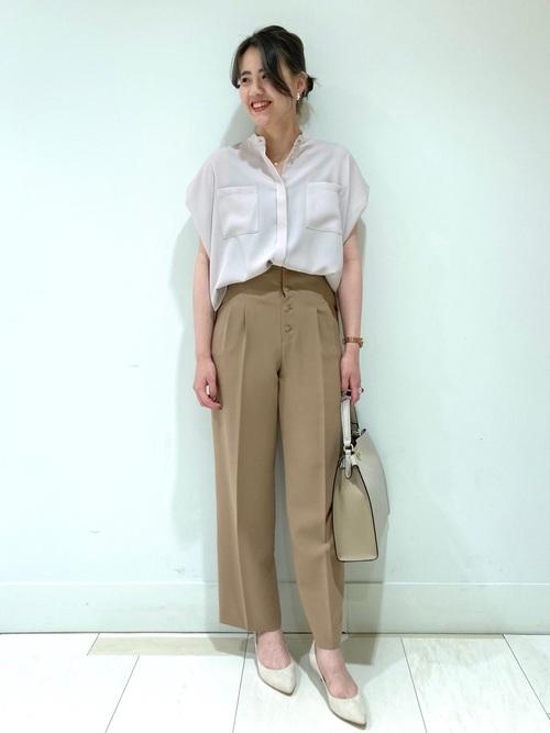 白ブラウスとベージュタックパンツに白パンプスを履いた女性