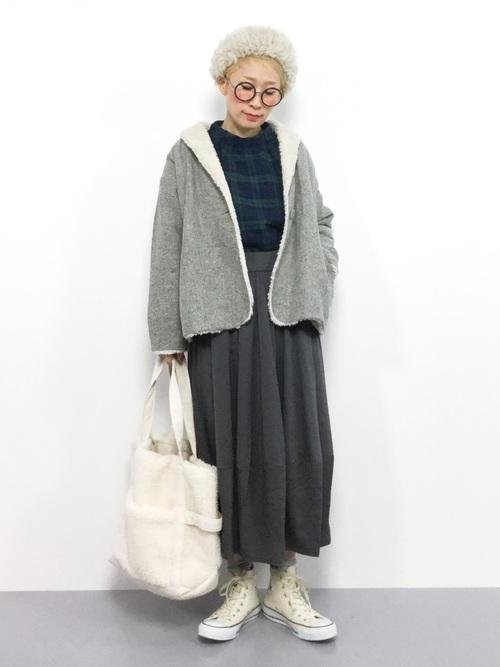緑チェックブラウスとグレームートンコートに裏起毛バルーンスカートを履いた女性