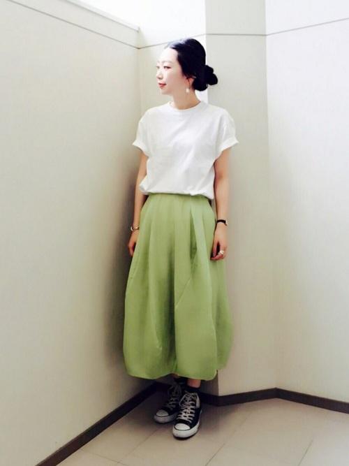 白Tシャツとグリーンバルーンスカートに黒スニーカーを履いた女性